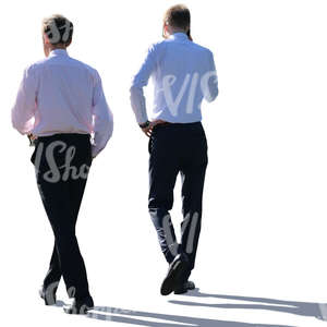 two backlit businessmen walking
