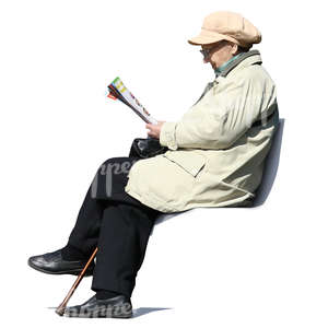 elderly woman sitting in a park and reading newspaper