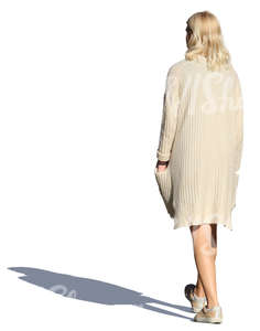 woman in a beige cardigan walking