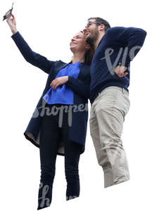 man and woman standing on a balcony and taking a selfie