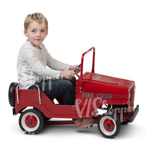 little boy driving a toy car