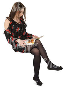 woman in a dress sitting and reading a magazine