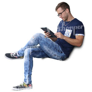 man sitting and looking at his tablet