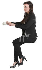 woman sitting at a counter and drinking coffee