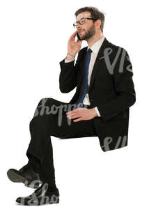 man in a black suit sitting and talking on a phone