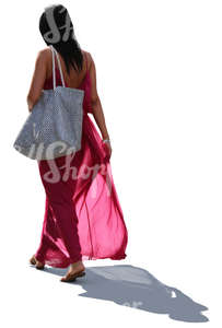 backlit woman in a long pink summer dress walking