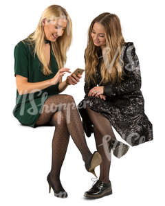 two women in party dresses sitting and talking