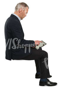 businessman sitting and checking his tablet