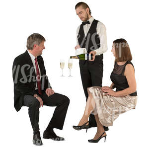 couple sitting in  a restaurant and waiter pouring out champagne