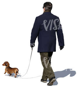 man in a dark blue coat walking a dog