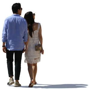 backlit asian couple walking hand in hand