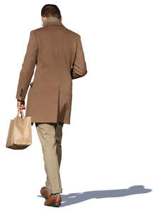 man in a light brown jacket walking