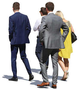group of people in formal clothing walking in sunlight