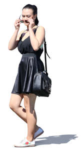 young asian woman in a black summer dress walking