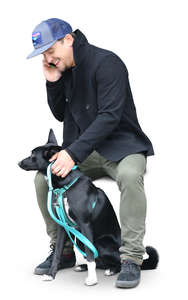 man sitting with his dog and talking on a phone