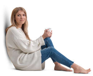 woman in a white pullover sitting and drinking coffee