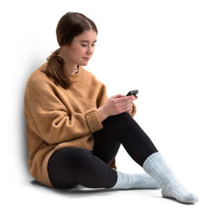 young woman in a sweater sitting and texting
