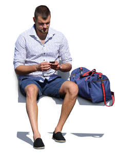 man with a gym bag sitting and texting