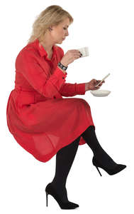 woman in a red dress sitting in a cafe and drinking coffee