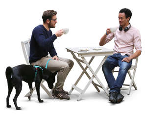two men and a dog sitting in a cafe