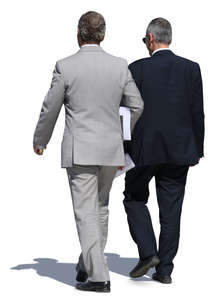 two older businessmen in suits walking side by side