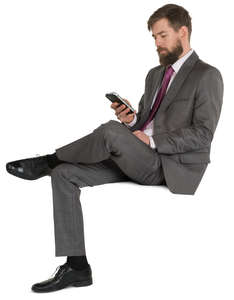 man in a fancy suit sitting and texting