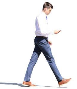 young businessman walking and looking at his phone