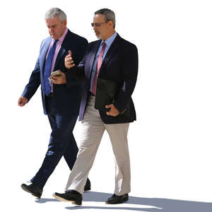 two backlit businessmen walking and talking