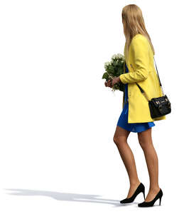 woman in a formal outfit walking with flowers in her hands