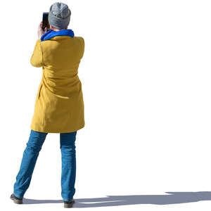 woman in a yellow autumn coat standing and taking a picture