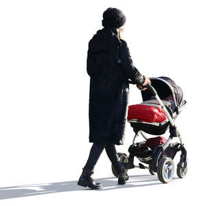 backlit woman in a black outfit walking with a baby carriage
