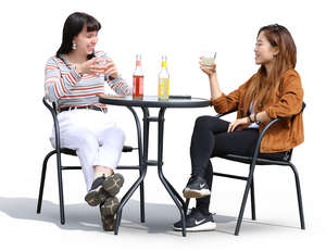 two women sitting and talking in a street cafe