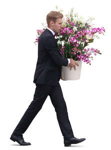 man in a black suit carrying a pot of flowers