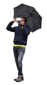 man with an umbrella taking a picture