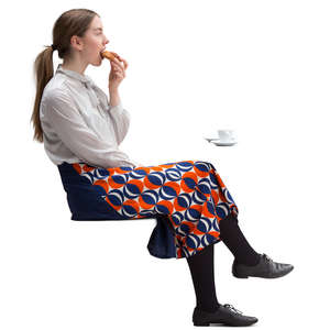 woman sitting in a cafe and eating danish pastry