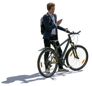 backlit teenage boy standing with a bike