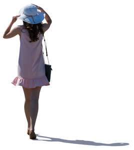 backlit woman in a pink summer dress walking