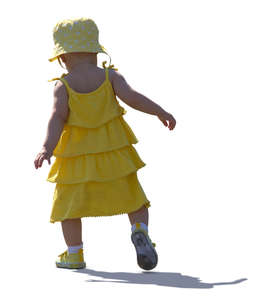 backlit baby girl in a yellow dress walking