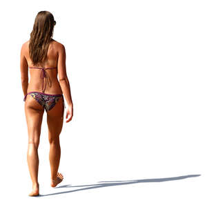 woman in a bikini walking barefoot on the beach