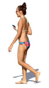 woman in a bikini walking and smiling