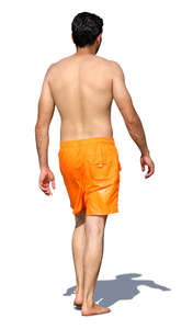 man in orange shorts walking barefoot on the beach