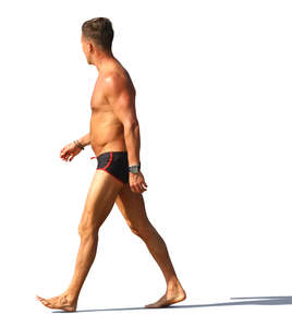 man in a swimsuit walking on the beach