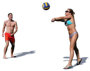man and woman playing volleyball on the beach