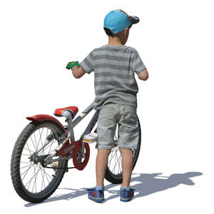 little boy standing with a bicycle
