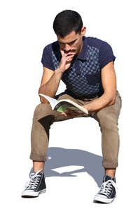 man sitting in sunlight and reading a book
