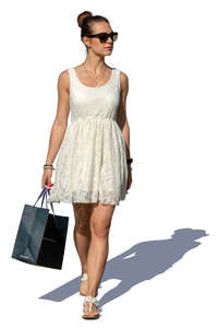 woman in a white summer dress with a shopping bag walking