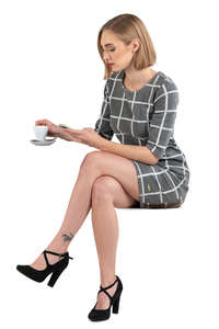 woman in a grey dress sitting in a cafe