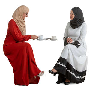 two muslim women sitting in a cafe and talking