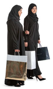 two muslim women with shopping bags walking