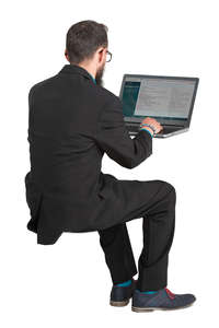 man in a suit sitting and working with laptop